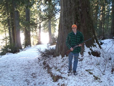 Tom posing with rifle, ready to hunt; next to a very large tree